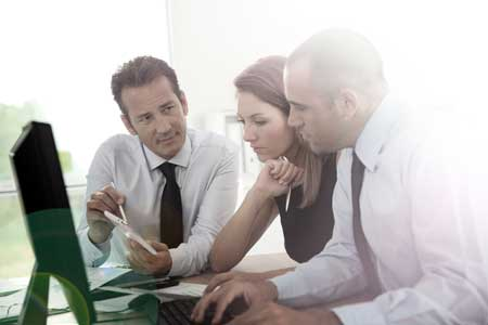 People in office discussing and looking at computer screen.